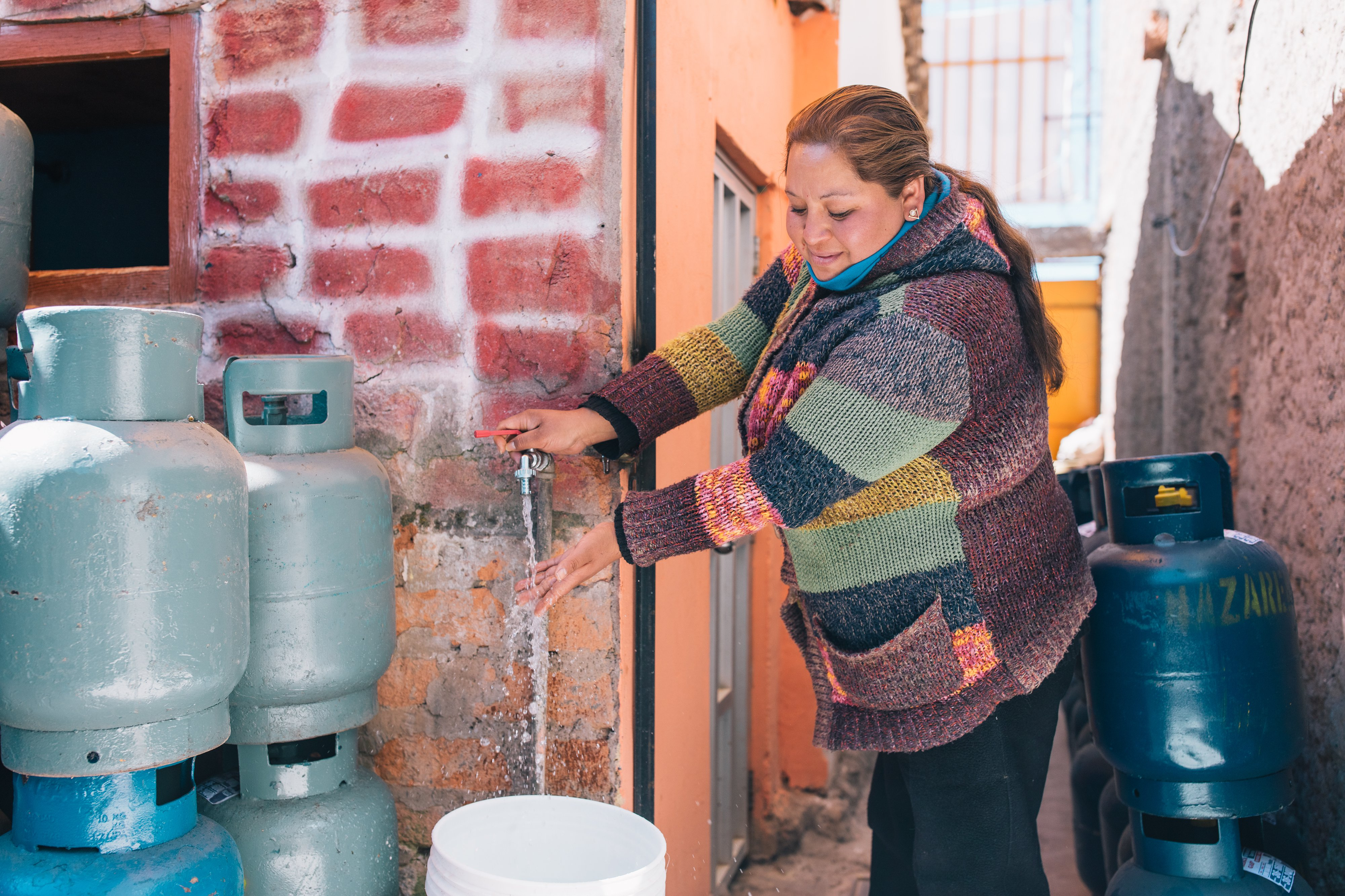 Peru - Woman pouring water from tap.jpg