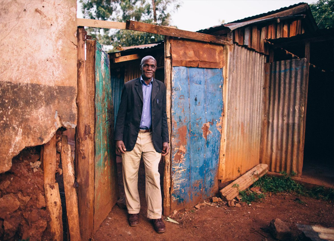 Gilbert stands in front of his home in Kigiru, Kenya