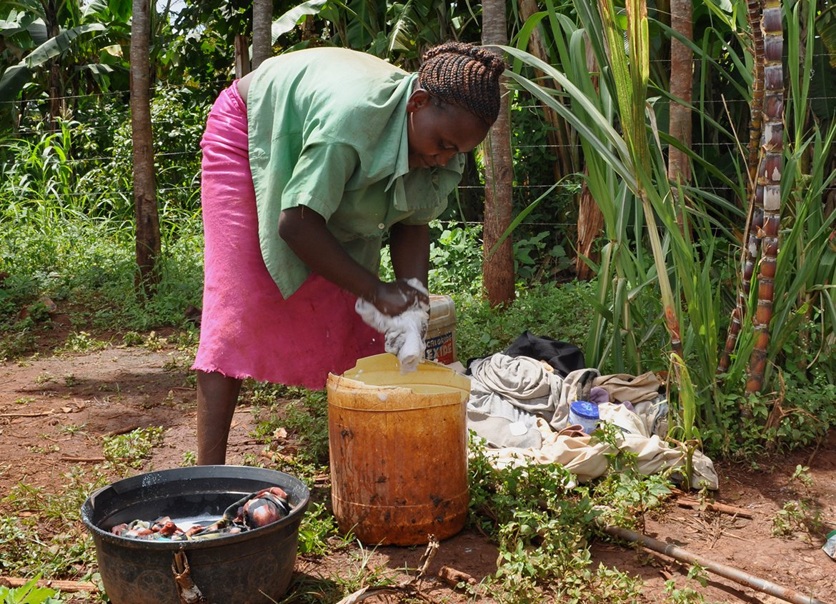 A woman uses a water tap installed near her home in Uganda