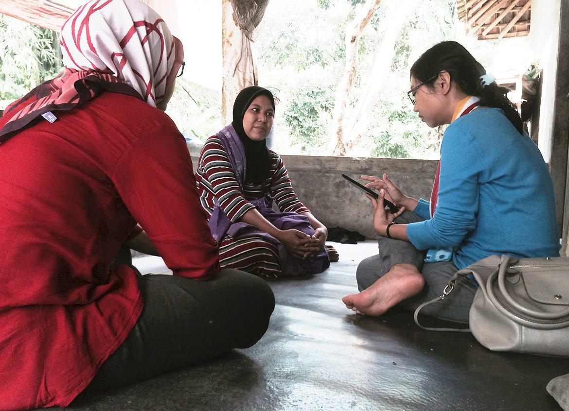 Water.org team members meet with a borrower in Indonesia