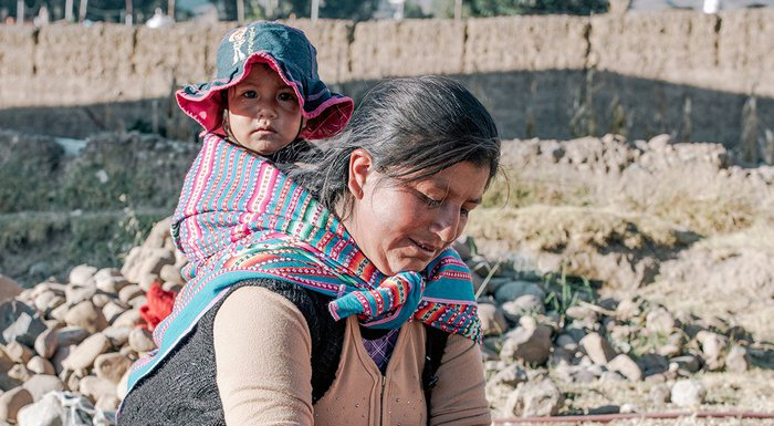 A mother uses a water connection in Peru