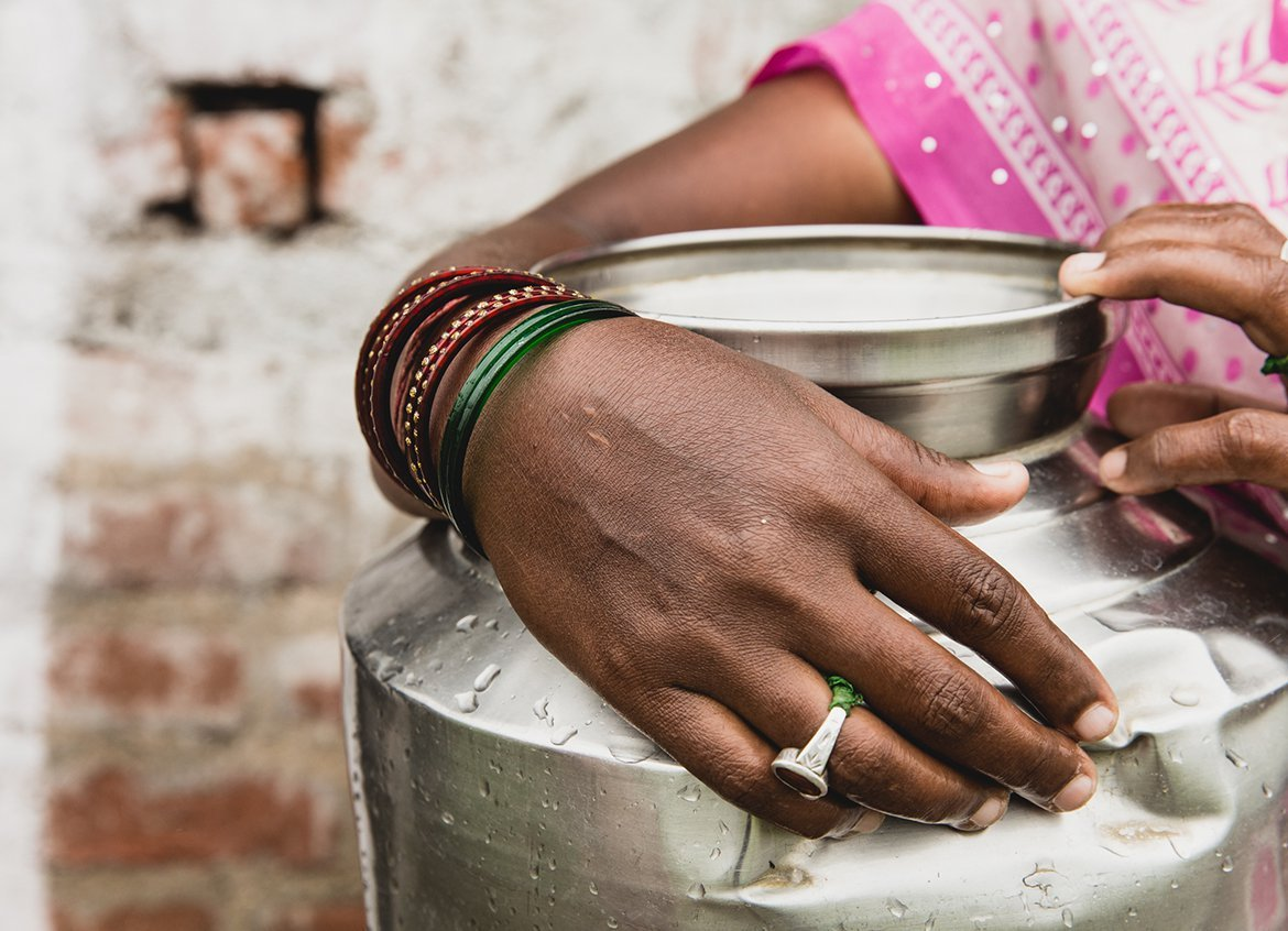 Woman holds a water vessel in India